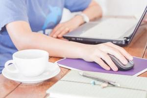 vrouw die op een laptop in een coffeeshop werkt