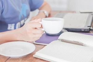 persoon aan het werk terwijl hij koffie drinkt