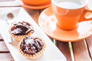 chocolade cupcakes en een oranje mok foto