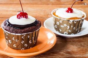 cupcakes van chocolade en boterconfituur versierd met rode kersen foto