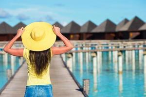 Maldiven, Zuid-Azië, 2020 - een vrouw die op een dok in de buurt van een resort aan de oceaan loopt foto
