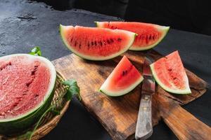 watermeloen plakjes in tweeën gesneden op een houten snijplank