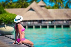 Maldiven, Zuid-Azië, 2020 - vrouw zittend op een houten steiger in een tropisch resort foto