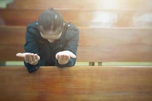mooie Aziatische vrouw die in de ochtend bidt in de kerk