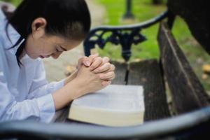 vrouw bidt met bijbel in de tuin
