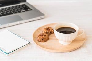 zwarte koffie en koekjes met laptop en notaboek