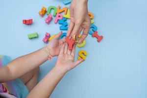 close-up handen van moeder en dochter die het alfabet bestuderen
