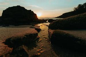 het water gaat door het pad in het zand foto