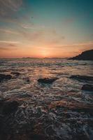 zee gaat door de rotsen onder een zonsondergang foto
