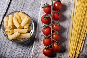 kerstomaatjes en verse pasta op een houten ondergrond foto
