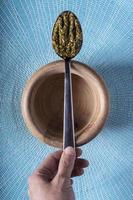 pesto lepel op een houten kom op een lichtblauwe achtergrond foto