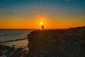 persoon die zich tijdens zonsondergang op rotsformatie dichtbij zee bevindt