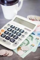 rekenmachine met geld en een kopje koffie op een grijze achtergrond foto