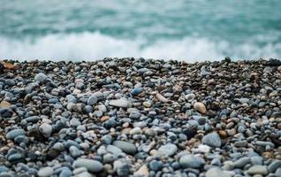 grijze en zwarte stenen in de buurt van zee overdag