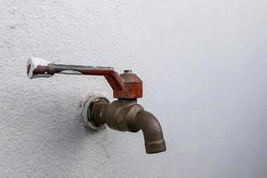 lege waterkraan naast de muur toont de droogte foto