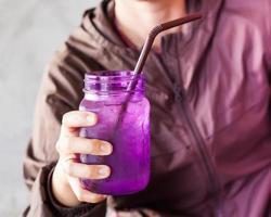 close-up van een persoon met een paars glas