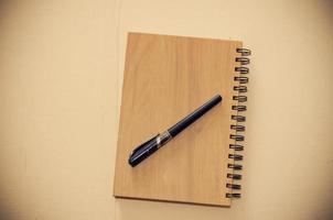 bovenaanzicht van een houten notitieboekje en pen