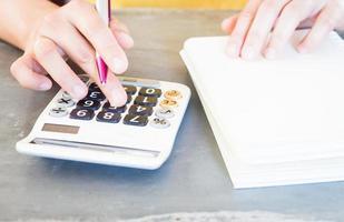 handen met een pen en drukken op de rekenmachineknoppen