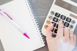 hand op een rekenmachine met een notitieblok