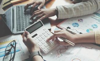 zakenpartners met behulp van rekenmachine en laptop