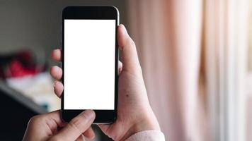 close-up van de hand van een vrouw met behulp van een slimme telefoon met een leeg scherm thuis