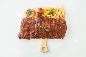 gegrilde bbq-ribben met groenten en frietjes op houten snijplank