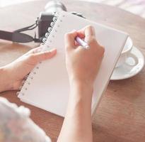 close-up van een vrouw die in een notitieboekje schrijft