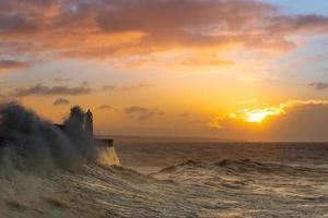 vuurtoren naast kust met zonsondergang achtergrond