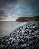 bewolkte dag op een stenen strand foto