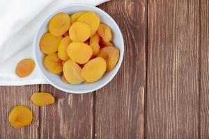 bovenaanzicht van gedroogde abrikozen in een witte kom op een houten achtergrond