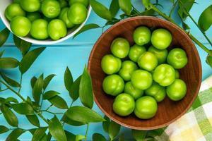 zure groene pruimen in kommen op een blauwe houten achtergrond foto