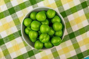 bovenaanzicht van zure groene pruimen in een witte kom op de achtergrond van een geruite stof foto