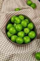 zure groene pruimen op geruite stof foto