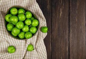kom met zure groene pruimen op geruite stof op donkere houten achtergrond foto