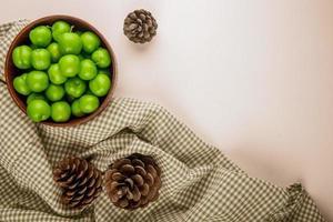 zure groene pruimen in een houten kom met dennenappels foto
