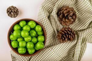 zure groene pruimen in een houten kom met dennenappels op geruite stof foto
