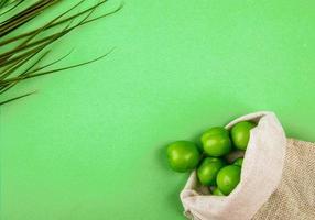 bovenaanzicht van zure groene pruimen in een zak op een groene achtergrond met kopie ruimte foto