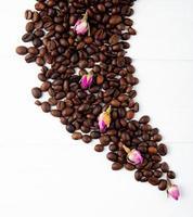 koffiebonen en thee roos toppen verspreid over een witte achtergrond