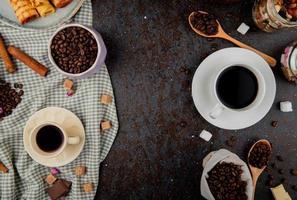 bovenaanzicht van koffiebonen en kopjes koffie op een zwarte achtergrond foto