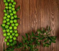 bovenaanzicht van zure groene pruimen met ruscusbladeren op een houten achtergrond
