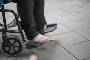 close-up van een oudere persoon in een rolstoel met pijnlijke voet