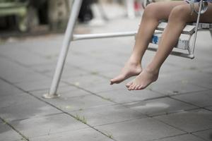 benen van kleine meisjes in een schommel in het park foto