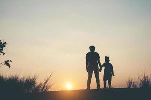 silhouet van vader en zoon die samen staan foto