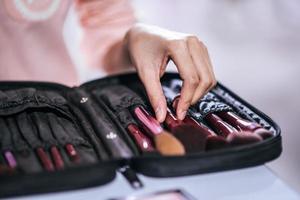 vrouw doet make-up met penseel en cosmetica