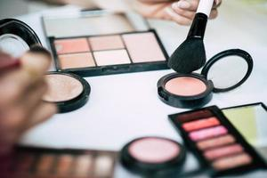 vrouwen die make-up met penseel en cosmetica doen