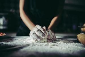 vrouw kneedt deeg voor pizza foto