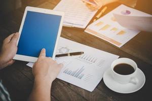 mensen uit het bedrijfsleven met behulp van tablet en grafieken tijdens vergadering