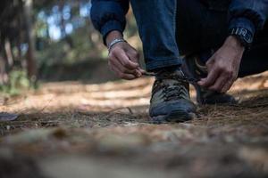 jonge wandelaar man knoopt zijn veters vast tijdens het backpacken in het bos