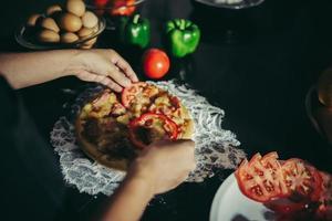close-up van een vrouw toppings op zelfgemaakte pizza te zetten