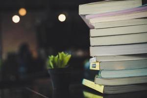 stapels boeken op een tafel op de achtergrond van een wazig bibliotheek